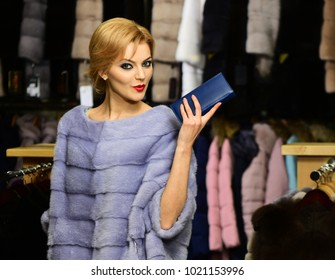 Girl with surprised face wears furry coat on clothes rack background. Lady with blue wallet tries expensive grey mink overcoat on. Rich fashion concept. Woman with blond hair buys furry coat.