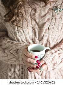 The girl in the sweater holding a Cup of coffee