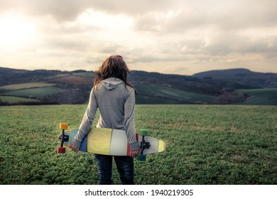 Girl in sweatshirt walking across green field towards hills (out of focus). Girl's hair flutters in wind and holds her colorful longboard in her hands. There are clouds in sky illuminated by sunlight.