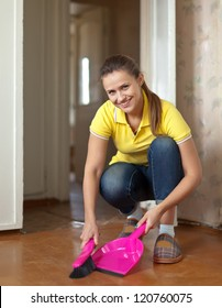 Girl sweeps the floor at home