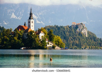 Girl swimming in Bled lake on a sunny day, zoom in