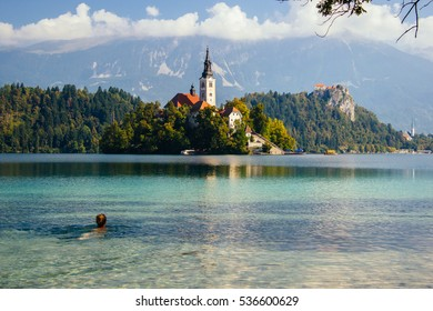 Girl swimming in Bled lake, zoom out
