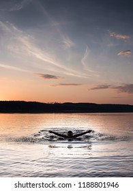 Girl swimming butterfly in lake night time nordic light