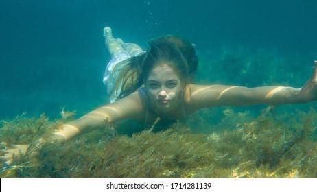 A girl swimming in dress underwater in sea
