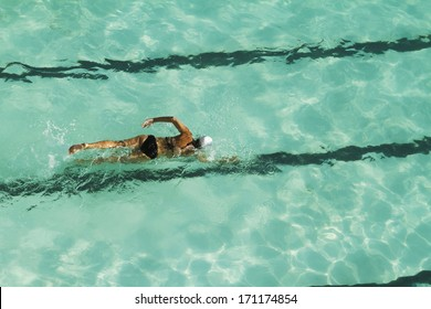 Girl swimming laps in a pool overhead view horizontal