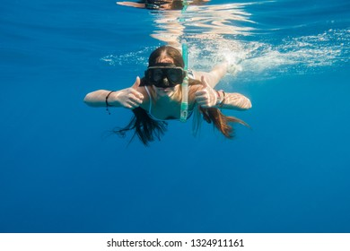 Girl in swimming mask dive in Red sea showing thumbs up, underwater shoot