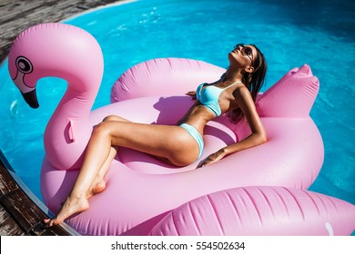 girl in swimming pool on inflatable flamingo