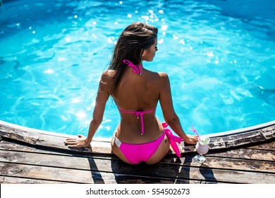 girl in swimming pool  in pink swimsuit