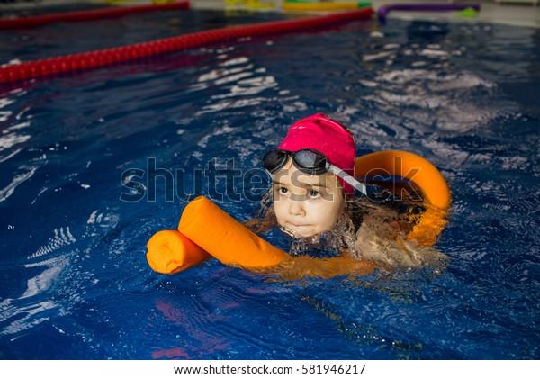 girl swimming using foam roller at swimming pool