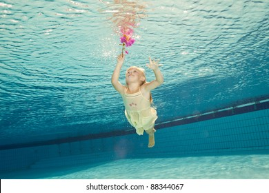 girl in the swimming-pool under water with a flower