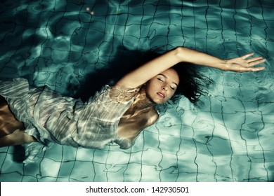 A girl swims in the pool at night