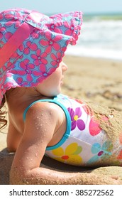 The girl in swimsuit  and hat  is  lying on the beach.