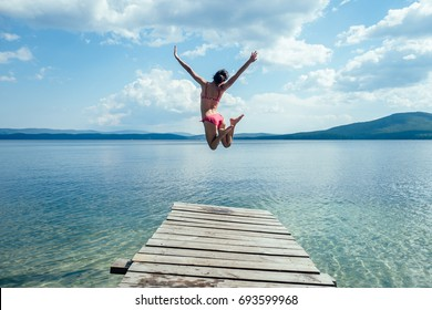 The girl in a swimsuit is jumping from a wooden pier into the water against the blue mountains. On the shore of the ocean, the sea, the lake. Happiness, summer, fun