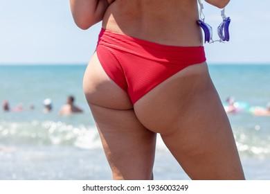 Girl in a swimsuit on the beach near the sea.