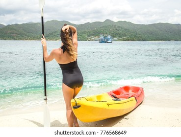 a girl in a swimsuit is sitting on the beach with a canoe