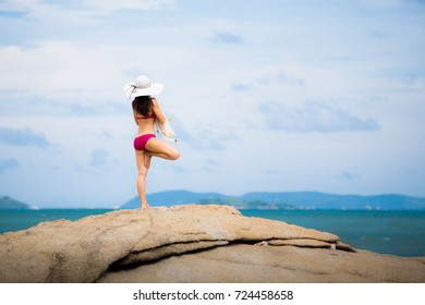 Girl in swimsuit Standing on the rocks on the beach in Pattaya. On a bright sky In the summer of Thailand. And she is happy.