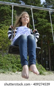 A girl is swinging  with long blond hair fluttering all around.