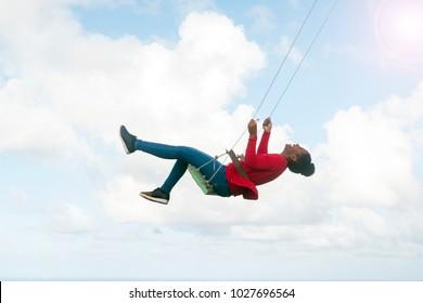 Girl swinging on a swing, clouds, sky
