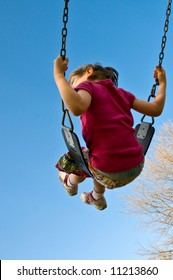 girl swings high into a blue sky vertical