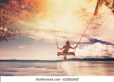 A girl swings on a swing and looks at the sunset on a tropical seashore. Freedom, rest, vacation, travel concept