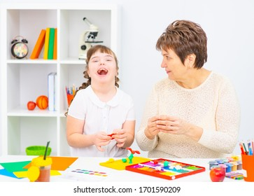 A girl with the syndrome and mom sitting at the table are engaged in creativity.