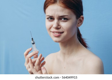 girl with a syringe in her hand on a blue background