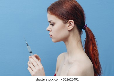 girl with a syringe in his hand on a blue background
