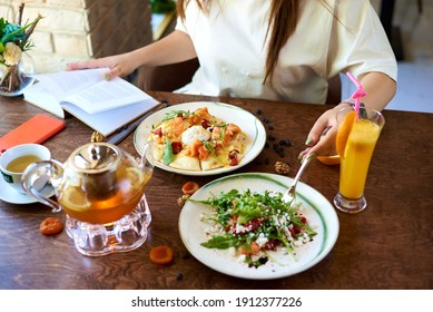 the girl at the table eats restaurant dishes