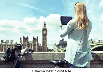 Girl with a tablet against UK Parliament