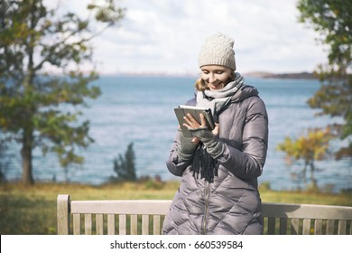 girl with a tablet in hands outdoors. Young woman in autumn park smiling, looking at tablet. The concept of WI-FI, technology and communication.