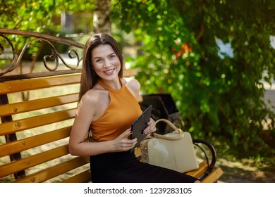 Girl with a tablet. Joyful and happy business woman sitting on a bench with a bag and a tablet