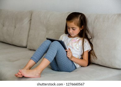 girl with a tablet on the couch
