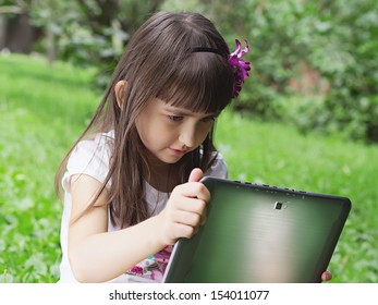 Girl with tablet pc in the meadow