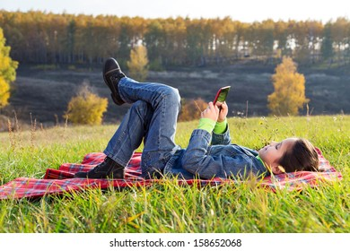 Girl with tablet pc on the autumn landscape, outdoors