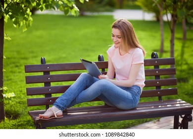 Girl with tablet sitting on a bench in the Park