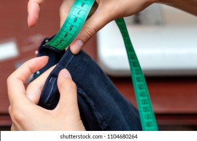 Girl tailor measures a centimeter seam leg.