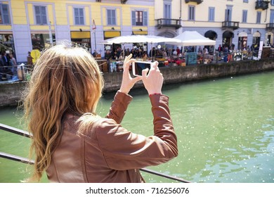 Girl take picture with her smartphone in Milano