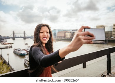 girl take a selfie in London with Tower Bridge on background