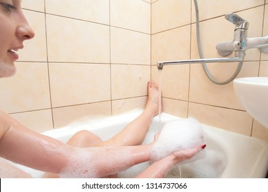 The girl takes a bubble bath, washes away the foam from her hands.