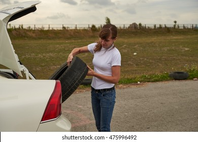 girl takes the car trunk the spare tire