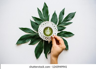 The girl takes in her hand a fresh healthy green matcha latte coffee in a beautiful mug on a white surface.