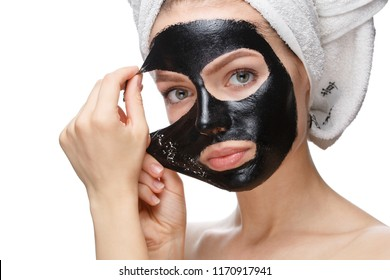girl takes off a black cosmetic mask from her face, Skin care face, isolated on a white background