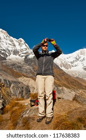 The girl takes photo of mountain landscape