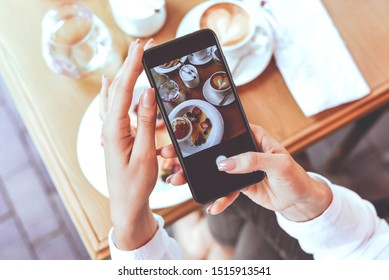 A girl takes photos of delicious food on the phone. Photo for the blog. Lifestyle. Blogger.Selective focus.