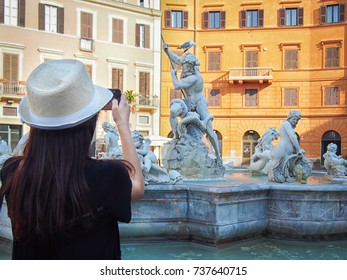 Girl takes a picture of the Fountain of Neptune (Fontana del Nettuno) in the Piazza Navona in Rome, Italy.