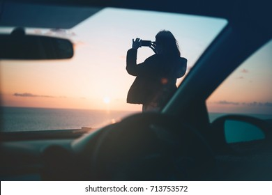 Girl takes a picture of a sunset as she enjoys driving her car in the nature