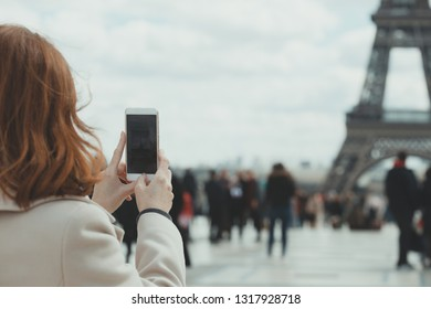 Girl takes pictures of a Eiffel Tower on a smartphone  in Paris. France