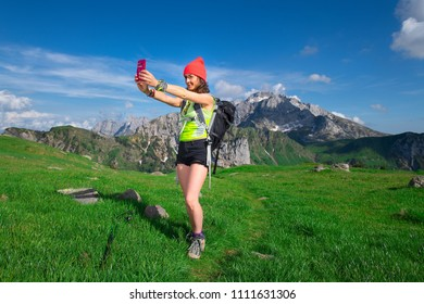 Girl takes a selfie while hiking in the mountains.