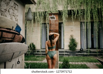 A girl takes a shower with fresh water on the beach or the street after sunburn, surfing and the sea Beautiful body, summer mood