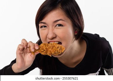 Girl taking a bite of fried chicken